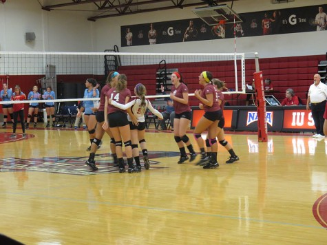 The Grenadiers celebrate winning a point in the fourth set in Thursday night's game against Oakland City.