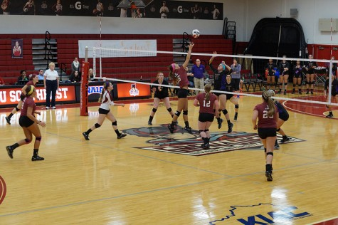 Junior outside hitter, Katie Fischer attempts to spike the ball on the St. Catharine front line.