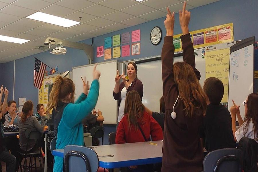 """(Standing) Shelby Royalty, education senior, teaches students a lesson about weathering in Susan Mosley's fourth-grade classroom at Corydon Intermediate School. """"We were making a W with our hands and then breaking it apart to show that weathering is the breaking of rocks,"""" Royalty said."""