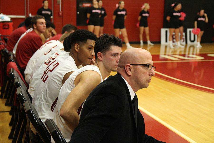 Jay Jones, assistant coach for the IUS men's basketball team sits on the bench with players during the game against St. Catharine. This is Jones' first year on staff.