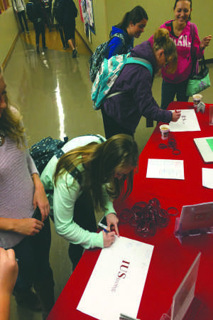 """Students make a pledge against sexual violence by signing their names and what made them """"IUStrong"""" on Wednesday, Nov. 11 as part of the It's On Us campaign."""