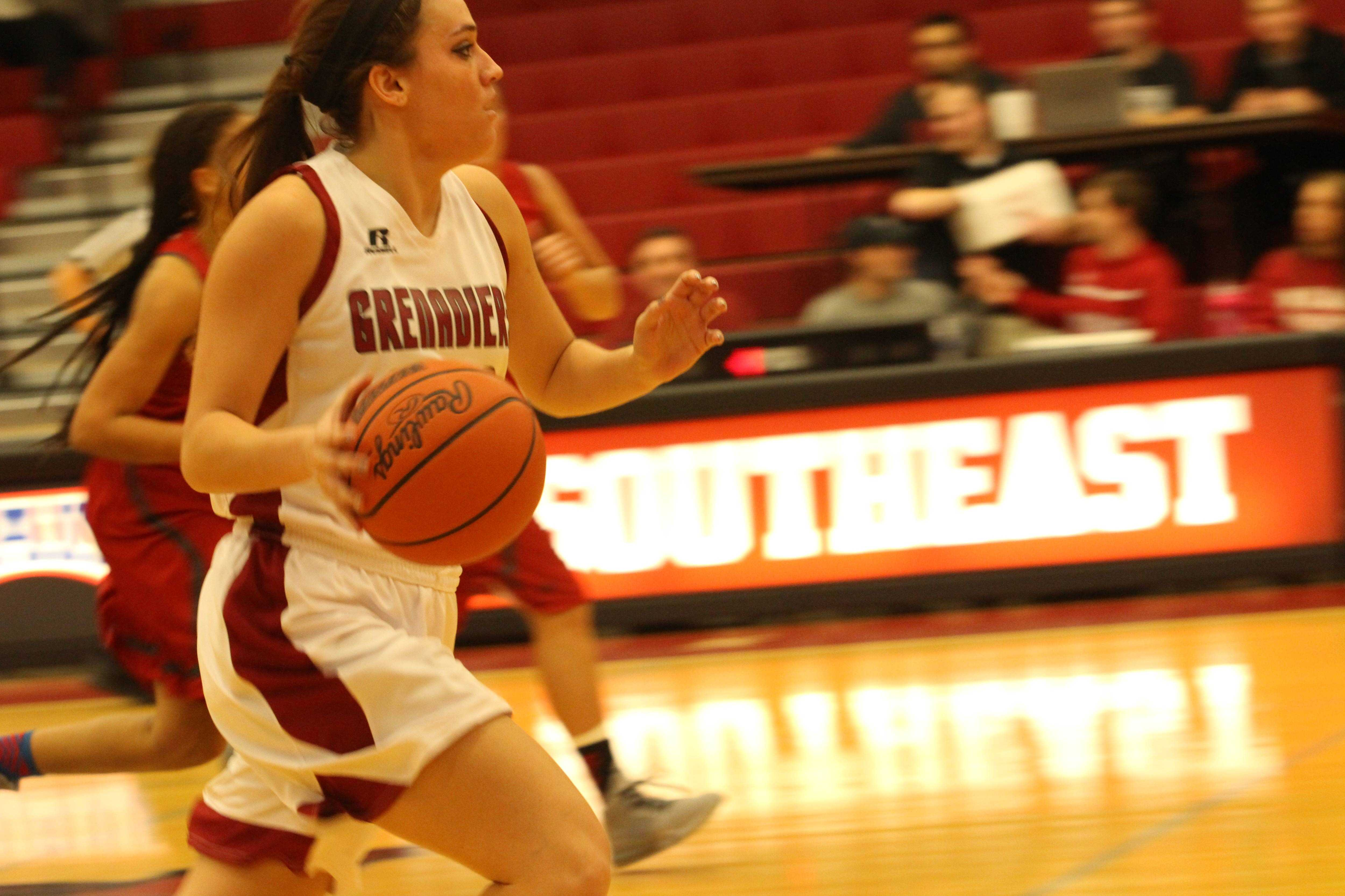 Junior forward Michaela Harris pushes the ball on a Grenadier fast break.