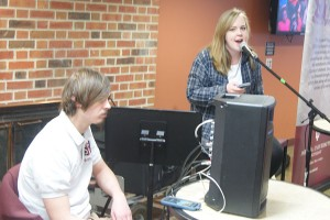 """Richard Stottman, music junior and arts and entertainment organizer of the SPC, monitors the speaker as Kelly Howard, psychology junior, sings """"I Want You To Stay"""" to students in The Commons during the SPC's Open Mic."""