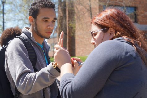 Bryan Simpson, psychology sophomore, lets Jordan Wingman, psychology sophomore, write NO H8 on his hand.