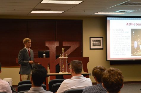 Dakota Brooks, education sophomore, discusses with potential members what Pi Kappa Alpha looks for when recruiting new members.