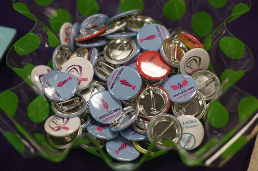 The+Center+for+Women+and+Families+pass+out+buttons+to+advocate+against+sexual+and+domestic+violence.