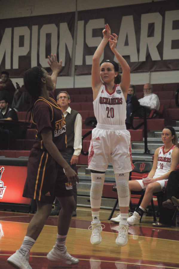 Madi+Woods%2C+sophomore+guard%2C+takes+a+three-point+shot+over+her+defender+against+Simmons+College.+