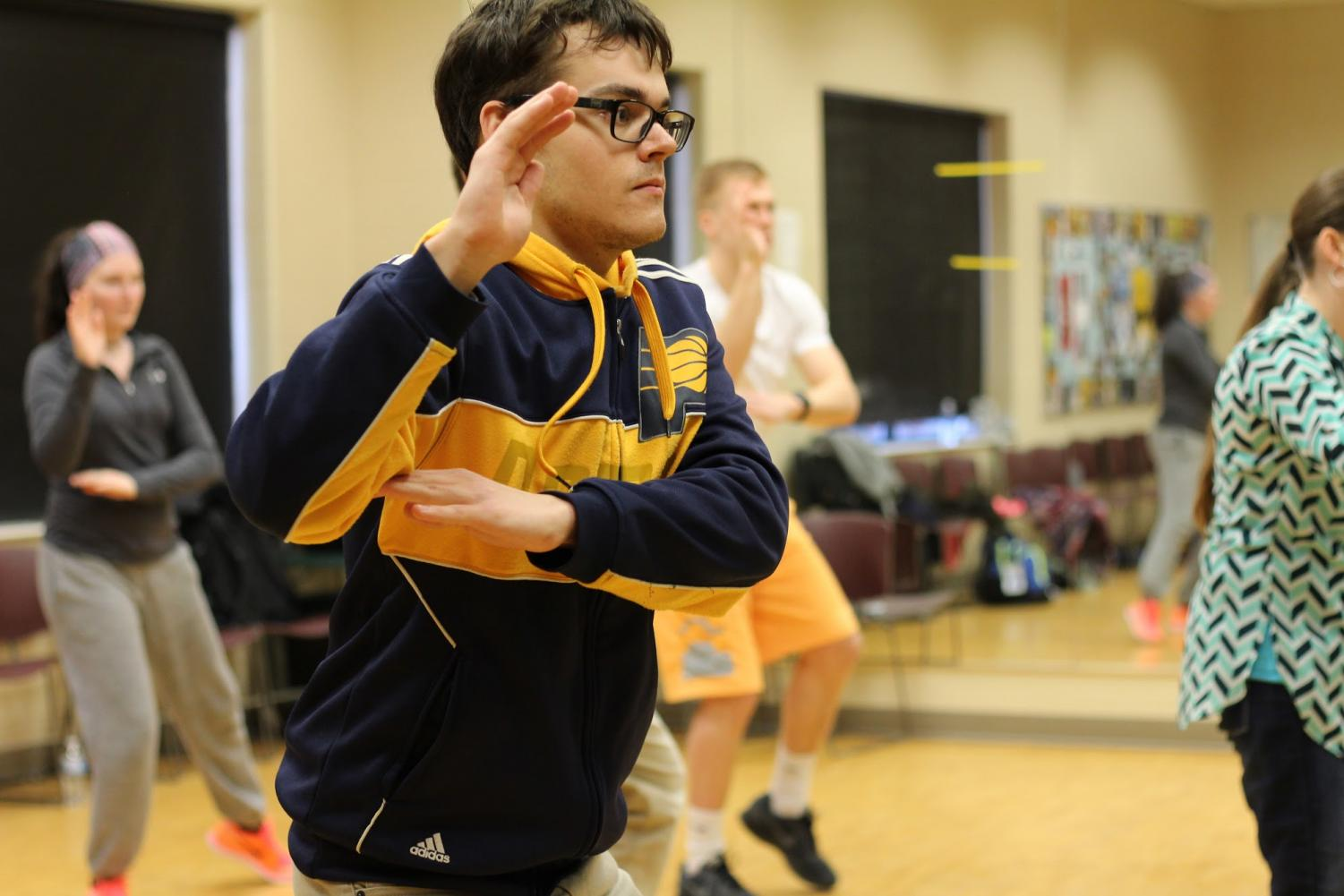 "Max Thieman, IU Southeast student currently taking Tai-chi Basics, warms up with a move called ""Hands in the Clouds."""