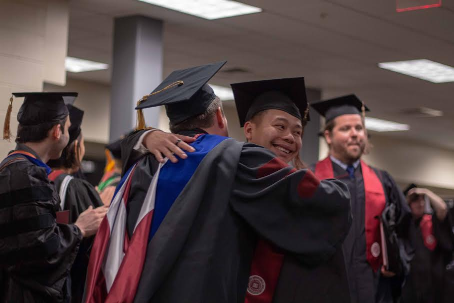 A student embraces a professor after receiving his diploma.