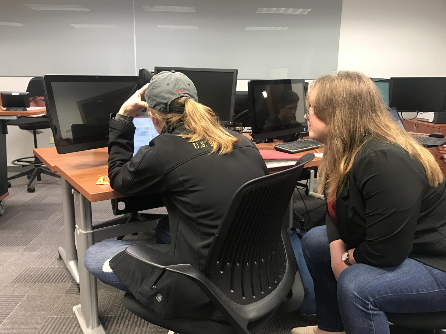 Sarah Caminiti, a business SI leader, assists Rachel Rozenboom, an international business sophomore, with an Access program project for Computer in Business.