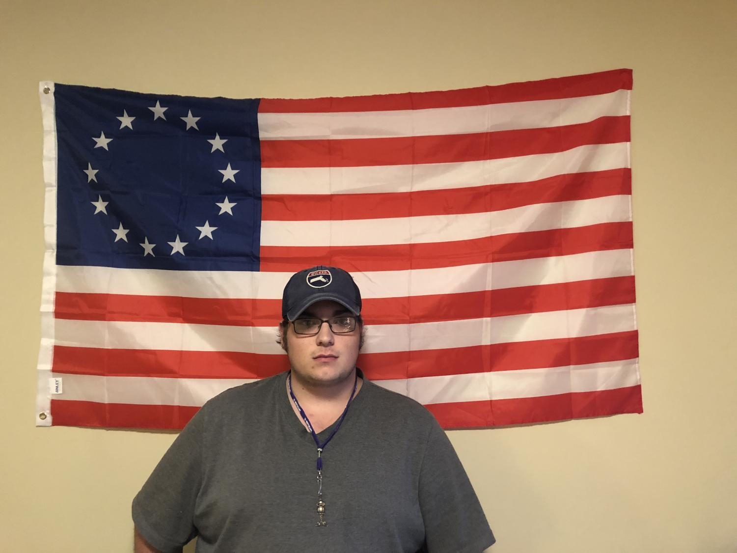 Austin Allen stands in front of the Thirteen Colonies flag that he brought to his IU Southeast dorm from his hometown in Massachusetts.