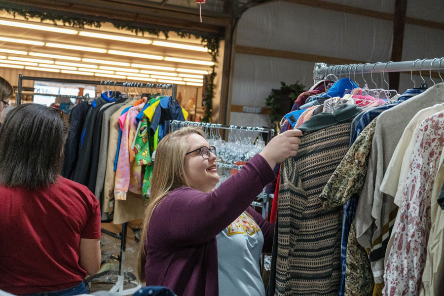 Betty+Collard+hangs+a+shirt+onto+a+rack+in+the+sorting+room.+Students+would+put+clothes+on+hangers+so+they+were+ready+to+be+sold+in+the+front+of+the+store.