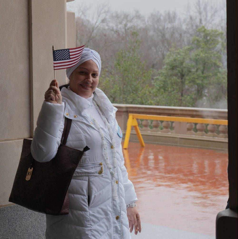 Cuban refugee Arianna Martinez waves an American flag to show support. Small American and Kentucky state flags were passed around to anyone that wanted one.