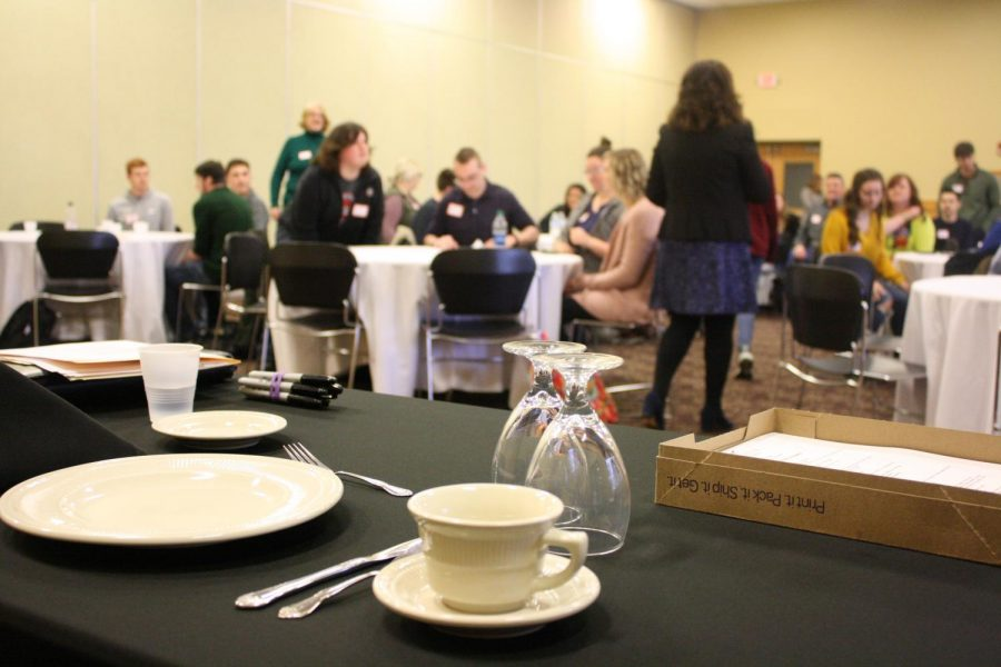 Places%2C+glasses+and+dining+utensils+are+center+stage+as+Mary+Starvaggi+speaks+to+students+in+the+Hoosier+Room+during+the+etiquette+workshop.