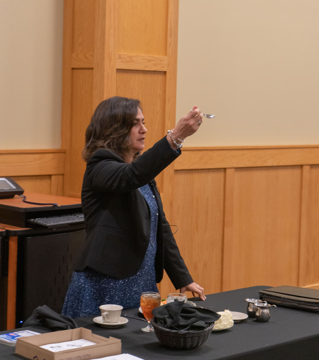 Mary+Starvaggi+holds+up+a+spoon+for+the+audience.+She+demonstrated+the+proper+use+of+every+utensil+on+the+table+during+the+lecture.