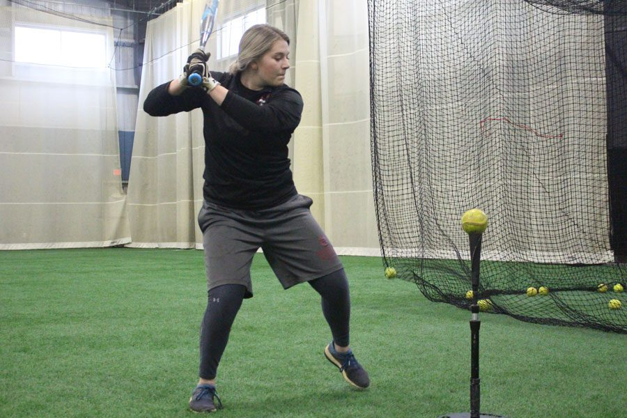 Sydney+Seger+loads+herself+up+before+hitting+off+a+batting+tee+during+batting+practice
