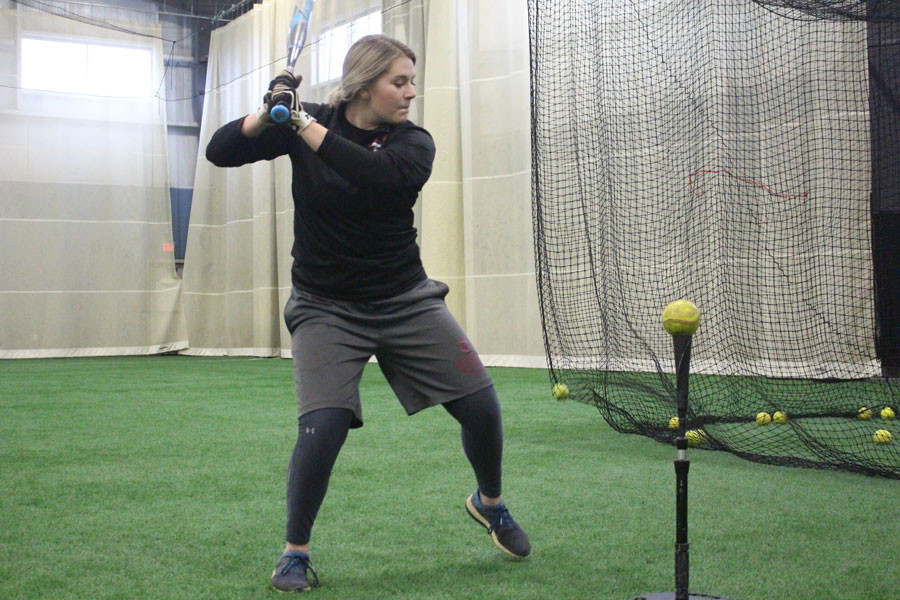 Sydney Seger loads herself up before hitting off a batting tee during batting practice