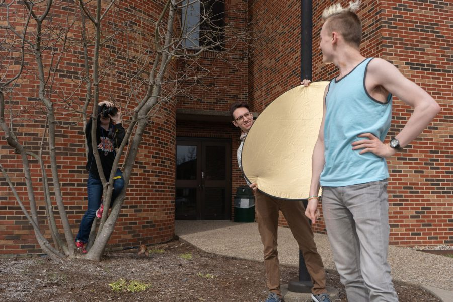 Junior Merlin Lee holds up a reflector while Junior Paris Brock takes a portrait of Junior Corgen Hobbs. Many projects in the Advanced photography class involve working in groups with one student acting as the model.