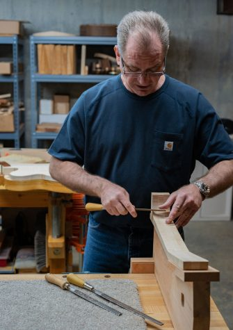 Mabe uses a file to shape an unfinished guitar neck. He hand shapes every piece of every guitar he makes.