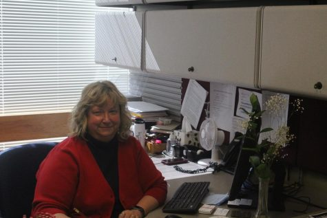 Kim Robertson poses at her desk in the Graduate Studies and Research office in the University Center. Photo by Tessa Arnold.
