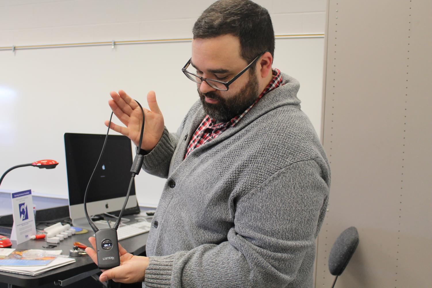 Danny Clements holds an assisted hearing device, which is one of the updated classroom technologies that has been implemented in the past few years thanks to the classroom budget.