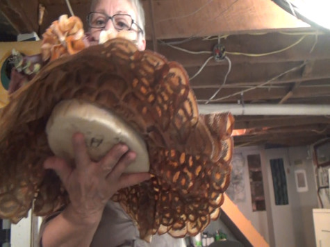Cudmore holds a hat she made from vegetables in her  studio