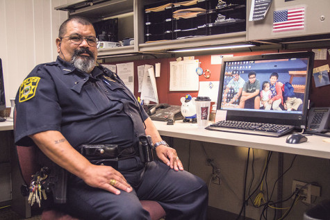 Officer Ruben sits at his desk in his office on campus.