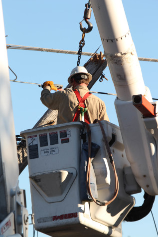 Duke Energy crews working to rewire the telephone poles and get power back to campus.