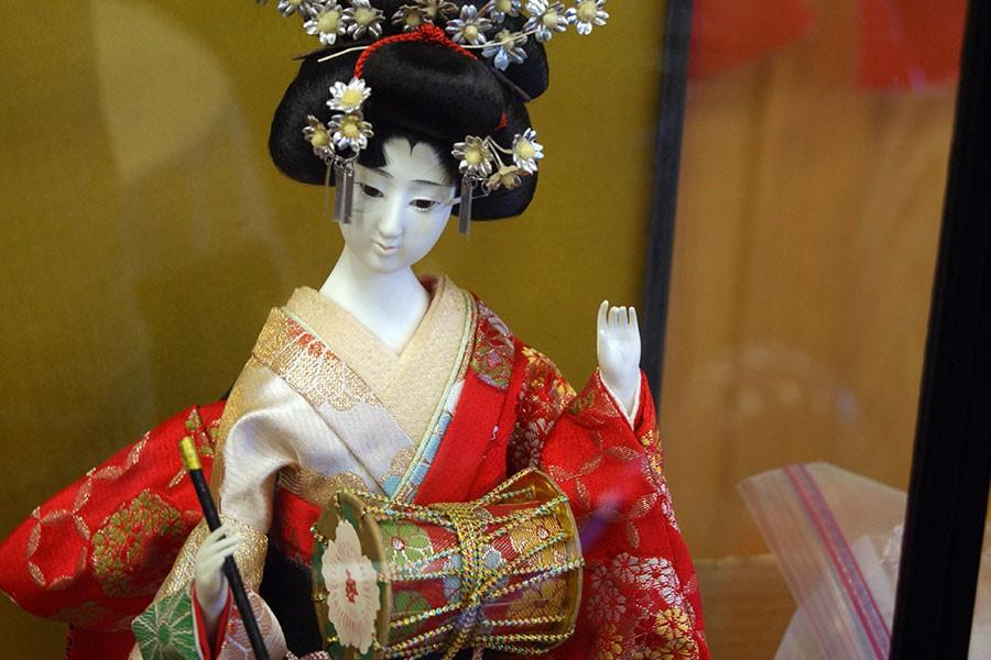 A+glass+cased+statue+of+a+Geshi%2C+the+name+of+a+performer+of+traditional+Japanese+theater%2C+on+display.%0A
