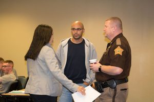 Jennifer Ortiz, visiting assistant professor of criminology, and her husband talk to Clark County Sheriff Jamey Noel prior to him addressing the students.