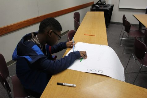 Student coloring a poster for a product design.