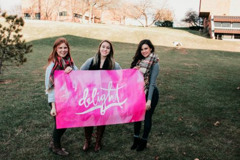Kiersten Baird, strategic communication sophomore, left, Sydney Nalley, graphic design freshman, middle, and Alex Meador, business-marketing junior, right, pose with their Delight flag as they kick off the new organization on campus.
