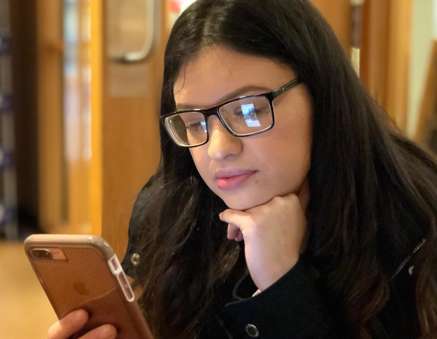 Angie Munoz, primary education sophomore, uses her phone during leisure time at University Grounds Coffee Shop. Photo by Meleena Richardson.
