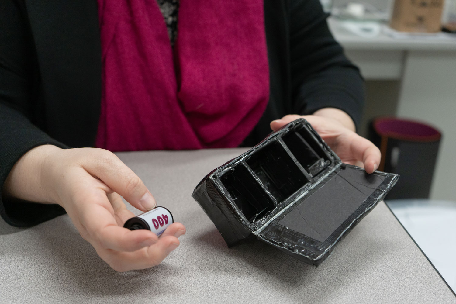 Amy Seibert holds out a roll of film and one of the makeshift pinhole cameras from camera club. The students used cardboard and duct tape to create their own film cameras and learn how to develop film.