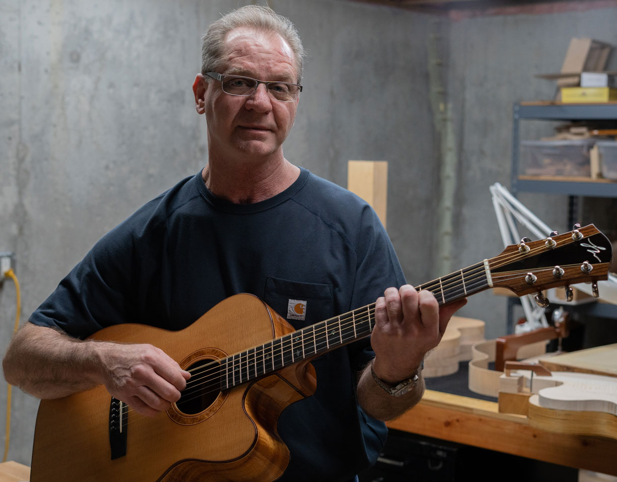"Mabe holds up the first guitar he made. ""I still play that guitar almost every week, and it's not the most comfortable guitar that I play, but I play it because I appreciate it, I appreciate the sound."""