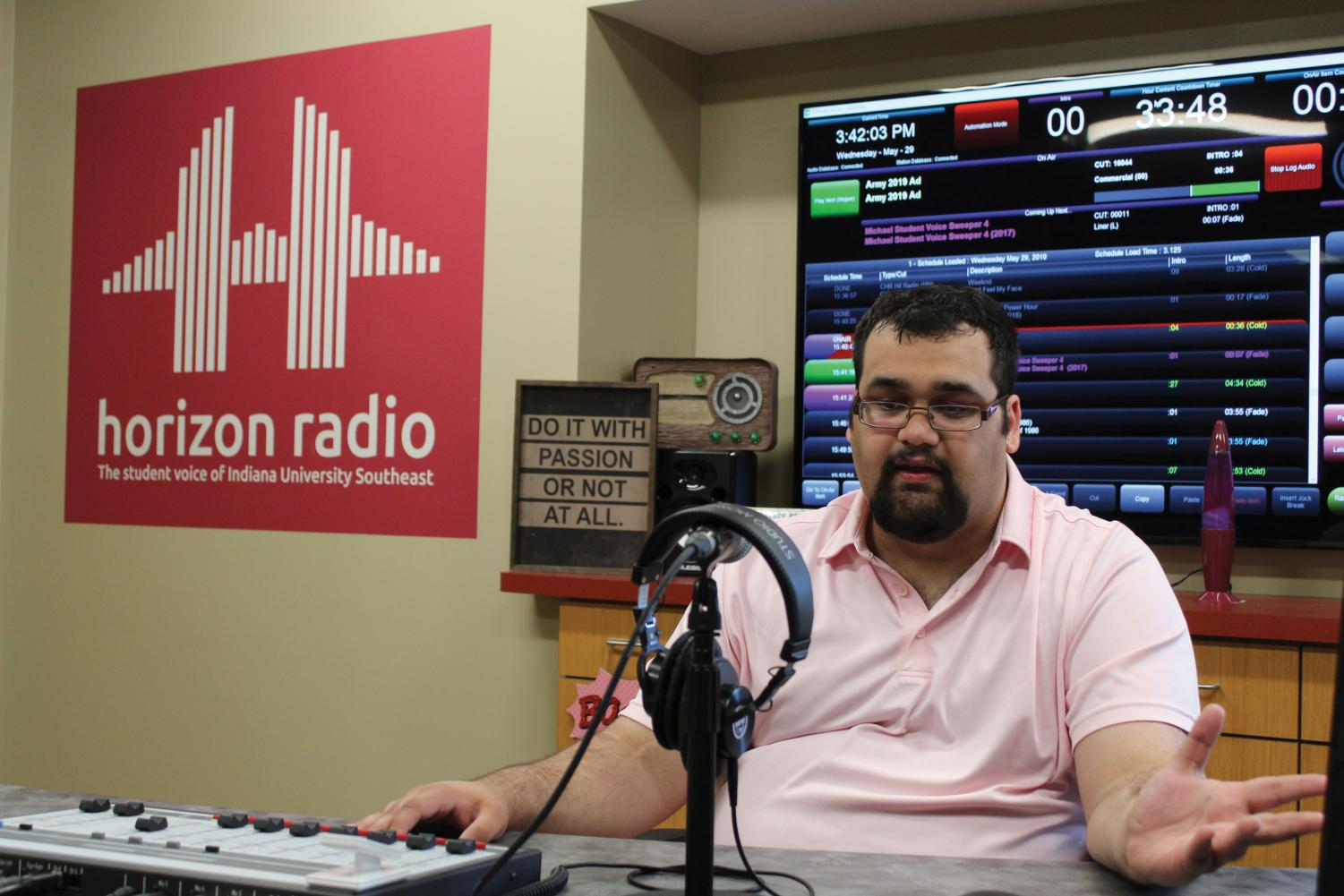 "Station Manager Matt McClellan mans the sound board inside Horizon Radio's broadcast room.  McClellan has led the station for three semesters. ""I enjoy hearing stories and talking to people and hearing what they have to say or play,"" he said."
