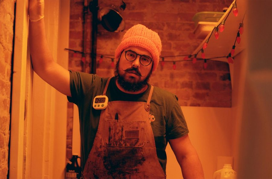 Rudy+Salgado+stands+in+his+darkroom%2C+a+repurposed+closet+dimly+lit+with+an+orange+safelight.+In+this+small+space%2C+Salgado+prepares+and+develops+his+tintype+photos.