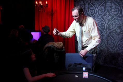 Professional sleight-of-hand magician Ken Abbot performs a coin trick for a captivated audience member during J&B's Thursday Night Magic Hangout.