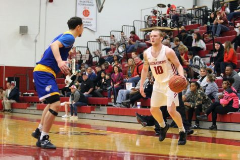Junior Guard Jared Osborne tries to drive against the Midway defender during the Grenadiers
