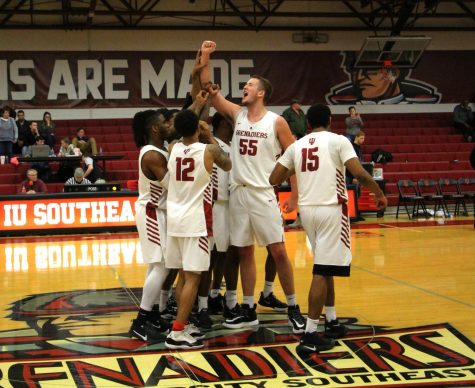 The Grenadiers huddle around senior center Seth Cox after their RSC West clenching victory over IU Kokomo.
